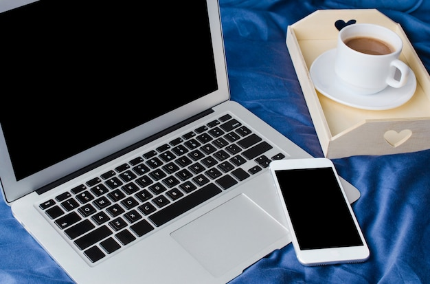 Laptop i smartfon, filiżanka kawy i notatnik na łóżku w czasie porannym. makieta.