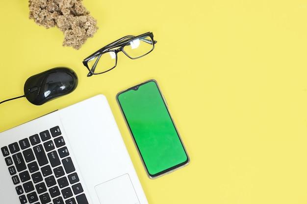 Laptop i smartfon na biurku na żółtym tle