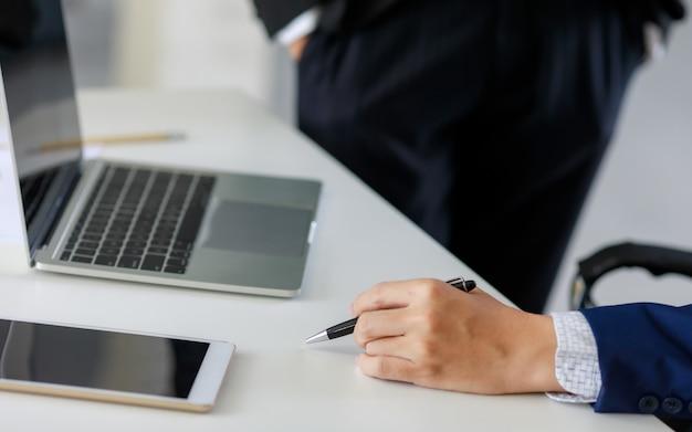 Laptop i tablet z ręką człowieka w granatowym kolorze, trzymając długopis na biurowym stole. pomysł na fajne, przytulne miejsce pracy.