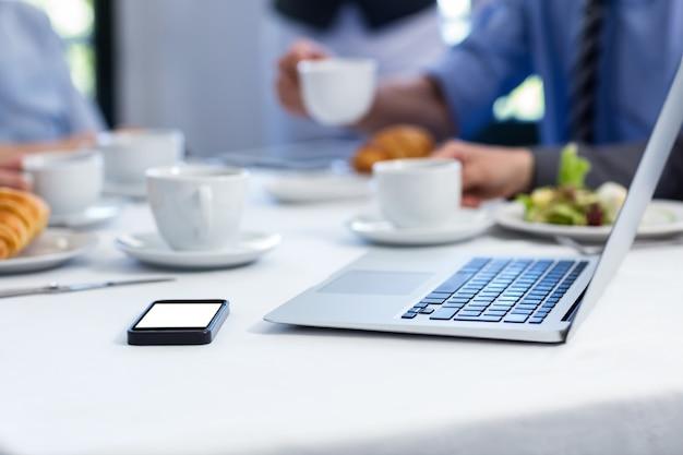 Laptop i telefon komórkowy na stole w restauracji