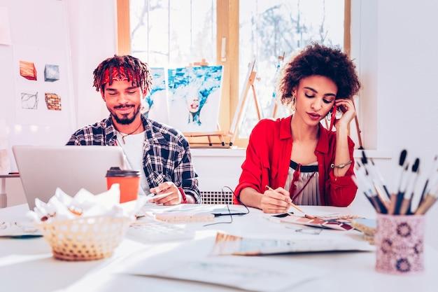 Laptop i telefon. mąż pracuje na laptopie, a żona dzwoni do klientów zamawiając obrazy