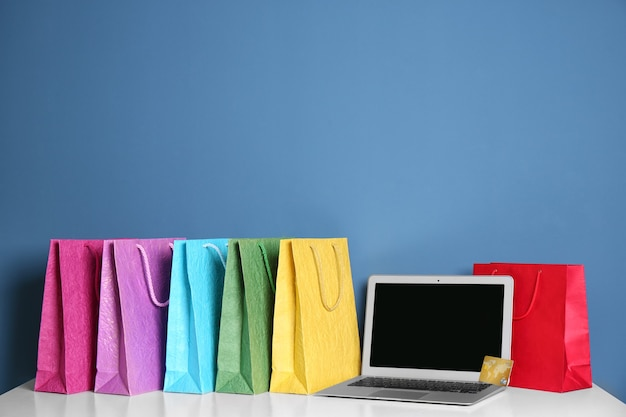 Laptop i torby na zakupy na stole na niebieskim tle