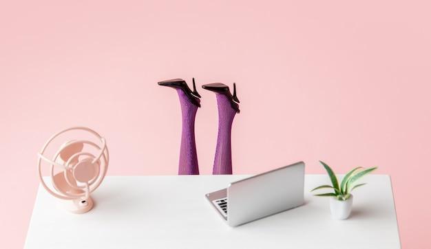 Laptop i wentylator na stole obok kobiecych nóg wystających spod stołu