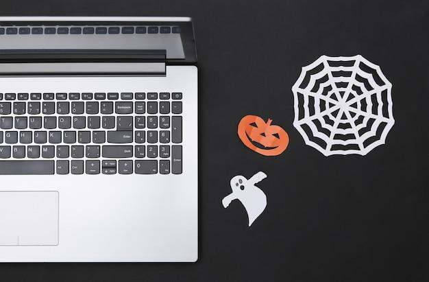 Laptop i wycinany z papieru wystrój halloween na czarnym tle. widok z góry. płaskie ułożenie