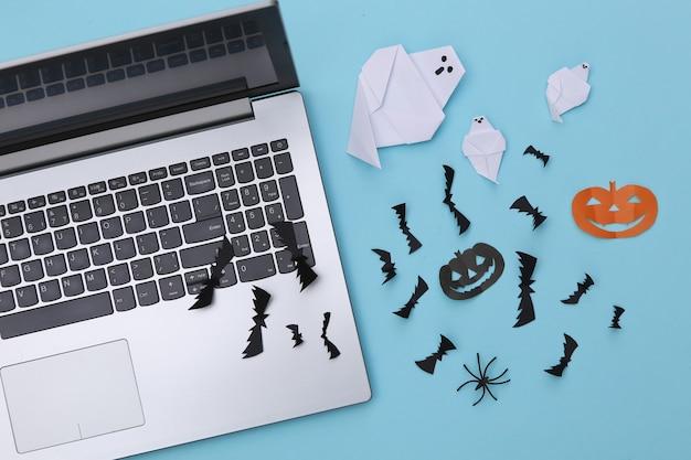 Laptop i wycinany z papieru wystrój halloween na niebieskim tle. widok z góry. płaskie ułożenie