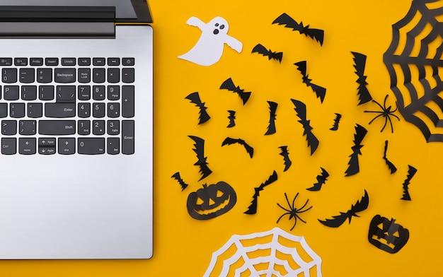 Laptop i wycinany z papieru wystrój halloween na żółtym tle. widok z góry. płaskie ułożenie