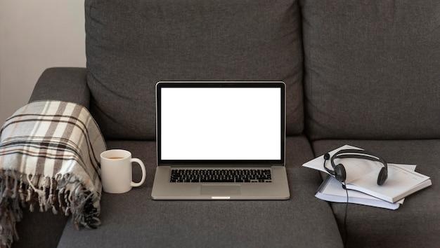 Laptop i zestaw słuchawkowy w domu na kanapie podczas kwarantanny