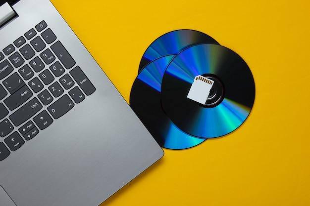 Laptop, karta pamięci sd, dyski cd na żółtym papierze o geometrycznych kształtach