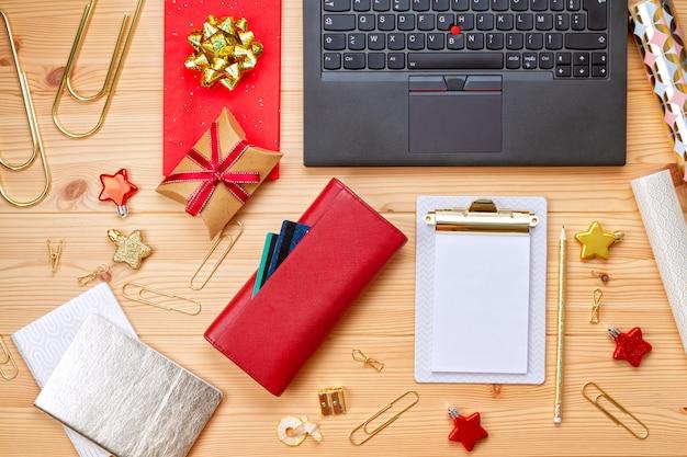 Laptop, karty kredytowe, torebka i świąteczna dekoracja. świąteczne zakupy online, kupowanie prezentów