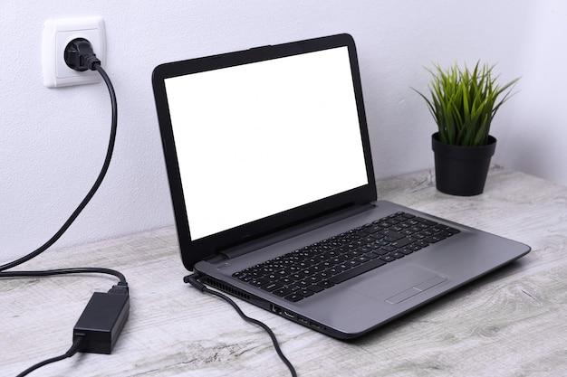 Laptop, komputer ładuje się z gniazdka o napięciu 220 v na biurku w pobliżu ściany. energia, akumulacja.