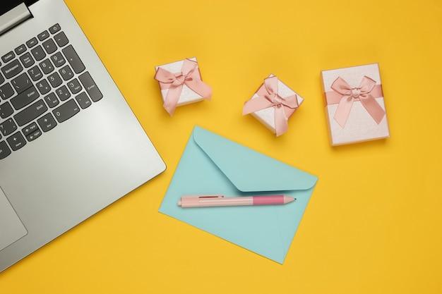 Laptop, koperta i pudełka prezentów na żółtym tle. boże narodzenie, walentynki, urodziny. widok z góry