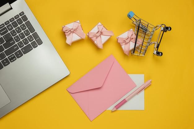 Laptop, koperta z listem i długopisem, pudełka na prezenty i wózek na zakupy na żółtym tle. boże narodzenie, walentynki, urodziny. widok z góry