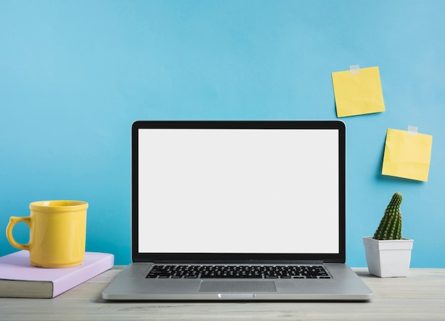 Laptop; książka i filiżanka kawy przed niebieską ścianą
