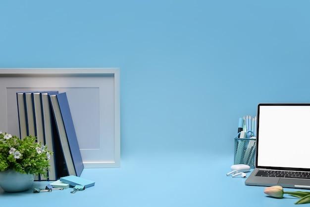 Laptop, książki, roślina doniczkowa i uchwyt na ołówek na niebieskim tle.