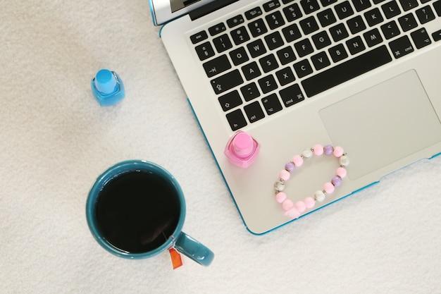 Laptop, kubek i lakier do paznokci