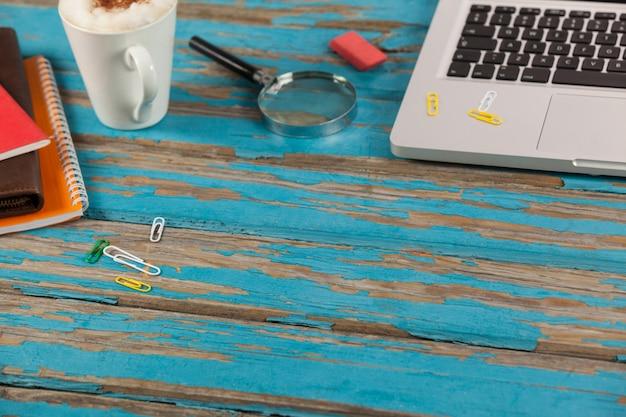 Laptop, kubek kawy, pamiętniki, szkło powiększające i papierowe szpilki