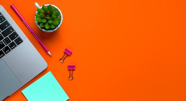 Laptop, kwiat, naklejki, spinacze, artykuły papiernicze na tle bujnej lawy. freelancer w miejscu pracy, biznesmen, przedsiębiorca, kobieta biznesu. transparent.