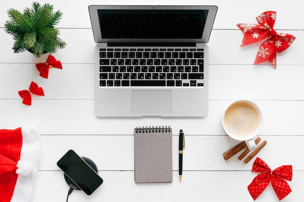 Laptop na białym drewnianym biurku otaczającym czerwonymi bożenarodzeniowymi dekoracjami, odgórny widok