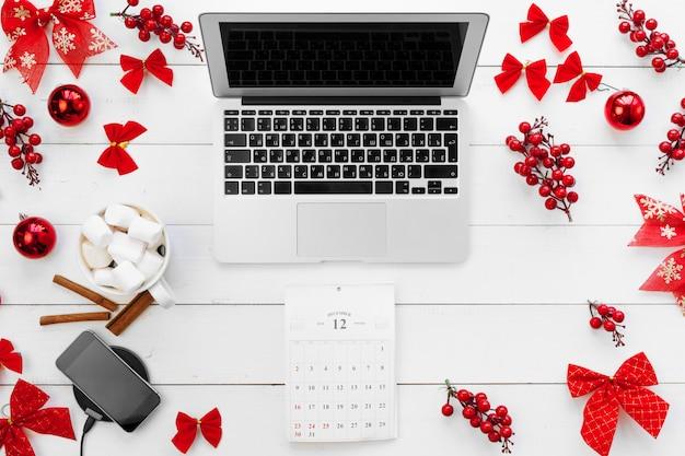 Laptop na białym drewnianym biurku w otoczeniu czerwonych ozdób choinkowych