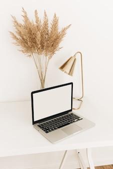 Laptop na białym stole ze złotą lampą i trawą pampasową