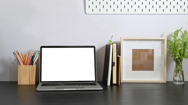 Laptop na biurku wraz z komputerem z białym pustym ekranem, książkami, notatnikiem, uchwytem na ołówek, ramką na zdjęcia, rośliną doniczkową układającą się na nim ze ścianą z białego cementu.