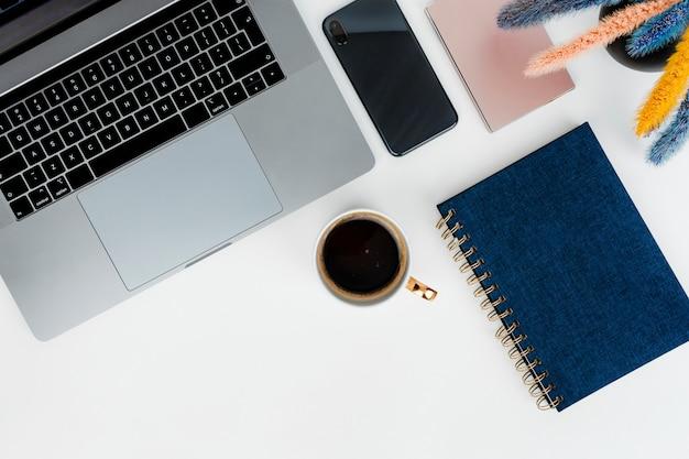 Laptop na biurku z niebieskim notatnikiem