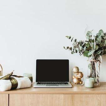 Laptop na drewnianym biurku ozdobionym bukietem eukaliptusa, pudełkiem prezentowym i świecami na białej powierzchni