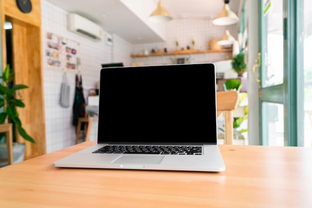 Laptop na drewnianym stole z ścinek ścieżką