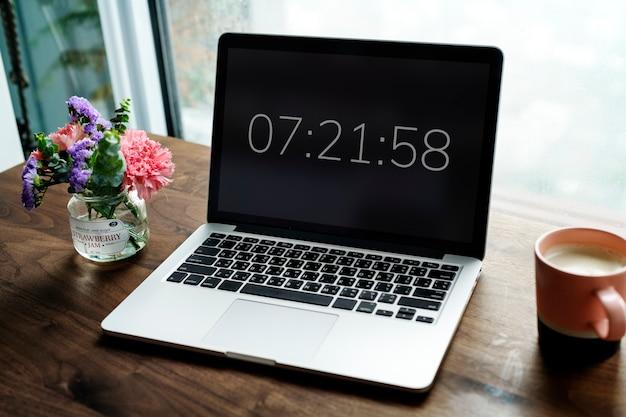 Laptop na drewnianym stole z zegarem