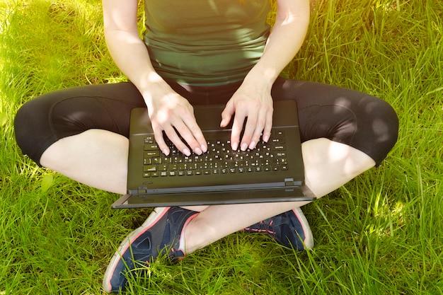 Laptop na kolanach dziewczyny na zielonej trawie.