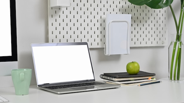 Laptop na obszarze roboczym z notebookiem, ołówkiem i filiżanką kawy.