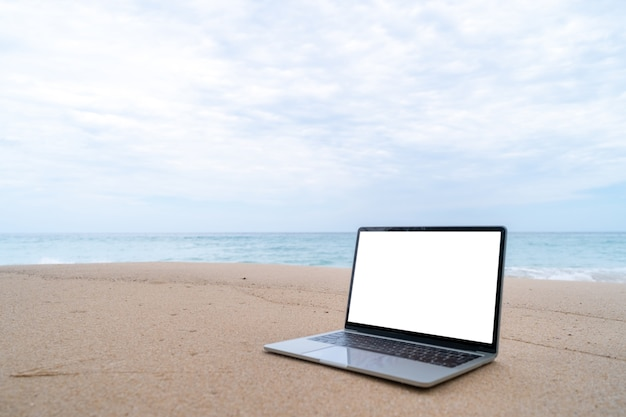 Laptop na piasku na plaży latem w tle.