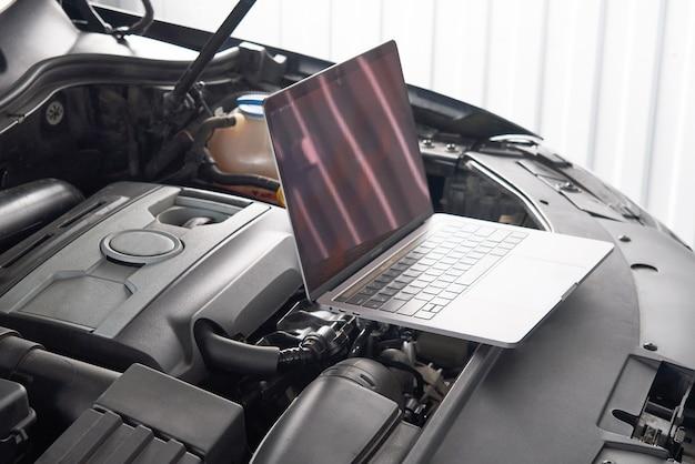 Laptop na samochodzie w auto remontowym sklepie, samochodu mechanika repairman pojęcie