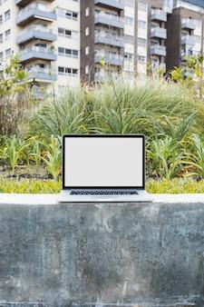 Laptop na ścianie oporowej przed mieszkaniem