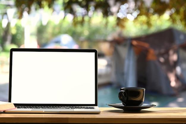 Laptop na składanym stole piknikowym w pobliżu namiotu na zewnątrz. pusty ekran dla wiadomości tekstowych lub treści informacyjnych.