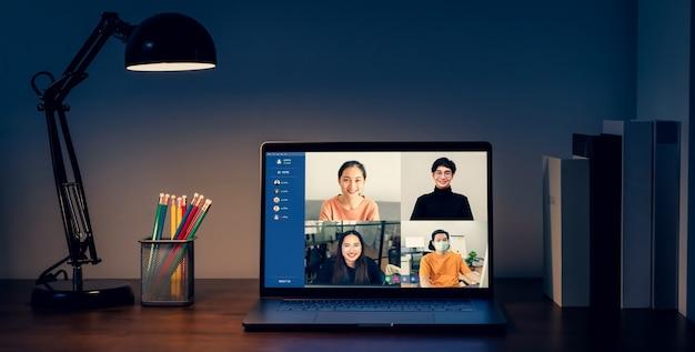 Laptop na stole w nocy z pokazem spotkania wideo z zespołem online i prezentacją projektów pracy. koncepcja pracy w domu.