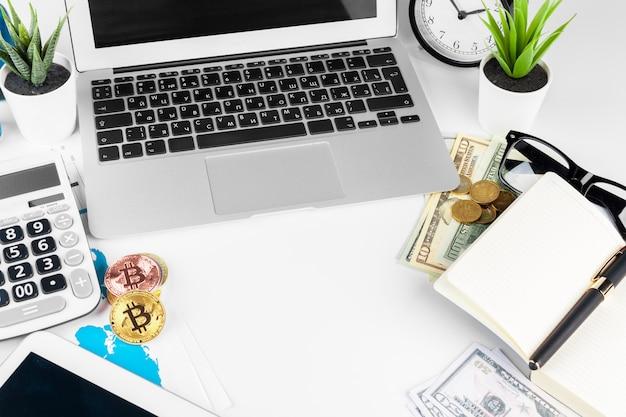 Laptop na stole w pobliżu dolarów i bitcoinów w biurze