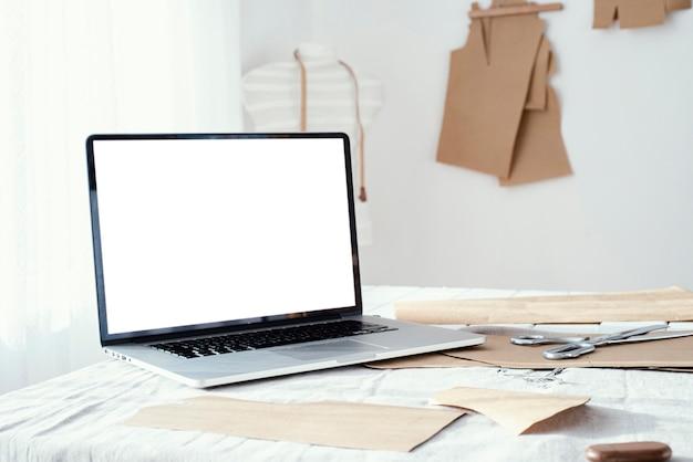 Laptop na stole w pracowni krawieckiej