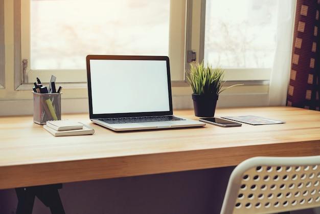 Laptop na stole w tle pokoju biurowego, do montażu wyświetlacza graficznego.