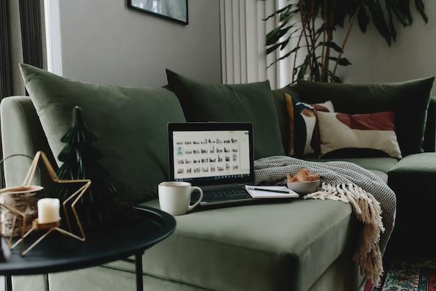 Laptop na zielonej kanapie. praca w domu. loft lub nowoczesne wnętrze.