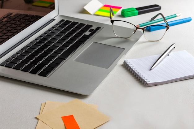 Laptop, notatnik i długopis, okulary, artykuły papiernicze na stole. praca w domu.