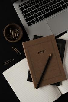 Laptop, notatnik, klipsy w drewnianej misce na czarno