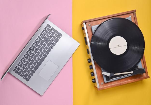 Laptop, odtwarzacz winylowy na kolorowym pastelowym tle. nowoczesna i nieaktualna technologia, widok z góry