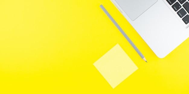Laptop, ołówek i notatnik kij na żółtym tle. leżał na płasko. skopiuj miejsce.