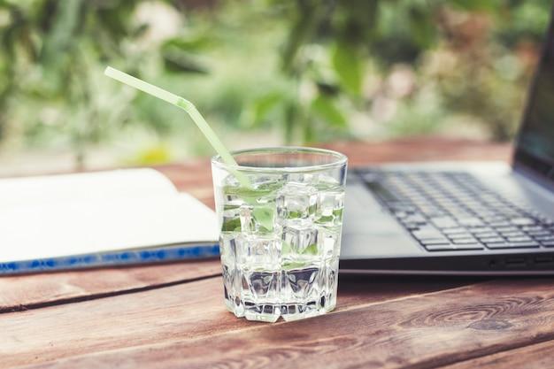 Laptop, otwarty dziennik i szklanka z orzeźwiającym zimnym napojem z kostkami lodu i liśćmi mięty na drewnianym stole. pojęcie pracy w naturze, wolny strzelec, praca na wakacjach