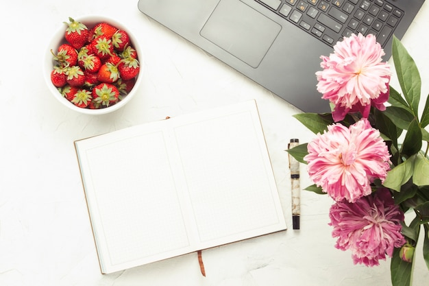 Laptop, pamiętnik i biały talerz z truskawkami na jasnym tle kamienia. koncepcja pracy w domu w przytulnej atmosferze. leżał płasko, widok z góry