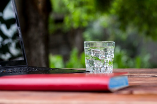 Laptop, pamiętnik i szklanka z orzeźwiającym zimnym napojem z kostkami lodu i liśćmi mięty na drewnianym stole. pojęcie pracy w naturze, wolny strzelec, praca na wakacjach
