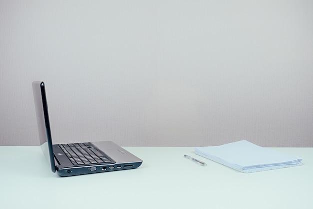 Laptop, papier i długopis na biurku w biurze
