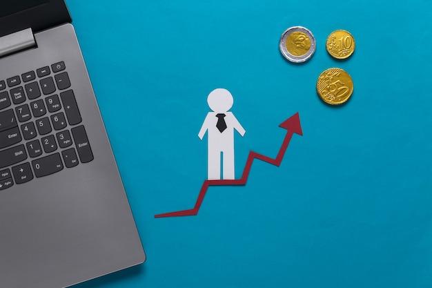 Laptop, papierowy człowiek biznesu na strzałkę wzrostu z monetami. niebieski. symbol sukcesu finansowego i społecznego, schody do postępu