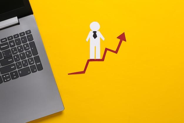 Laptop, papierowy człowiek biznesu na strzałkę wzrostu. żółty. symbol sukcesu finansowego i społecznego, schody do postępu